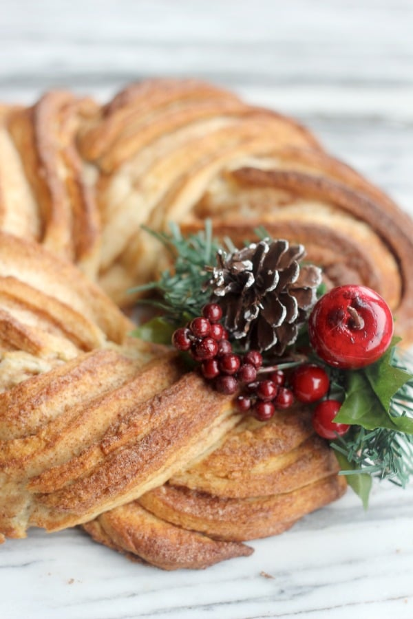 Cinnamon Roll Wreath decorated with holiday berries and garland