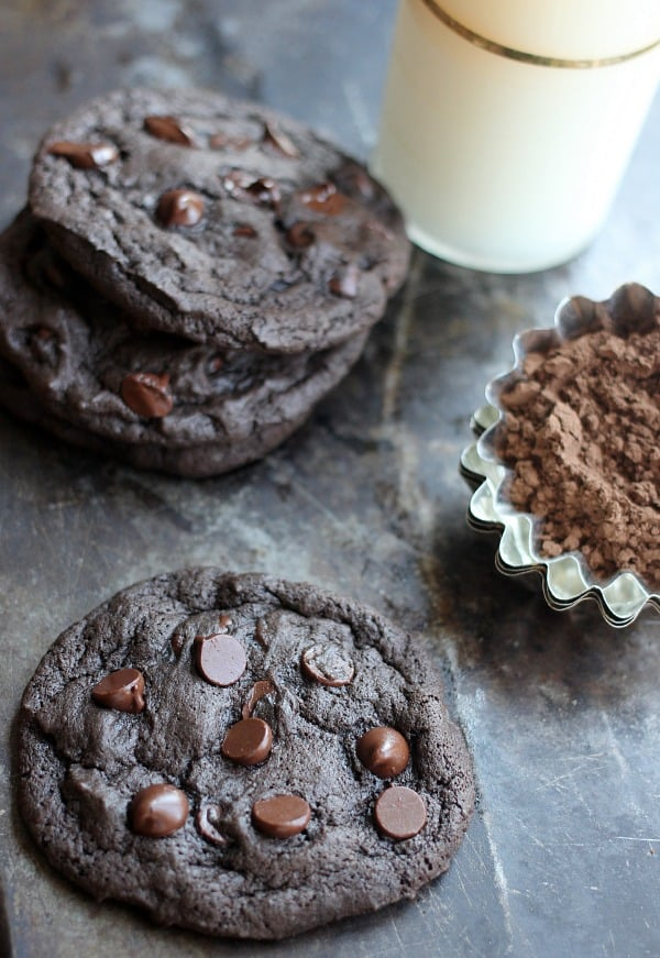Spicy chocolate cookies on a sheet pan with a glass of milk