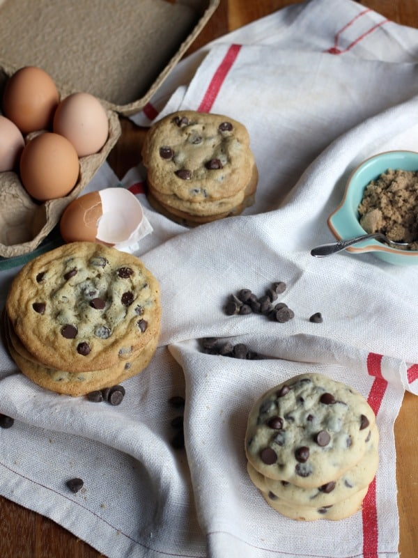 Cookies stacked up on a cloth beside raw eggs and chocolate chips