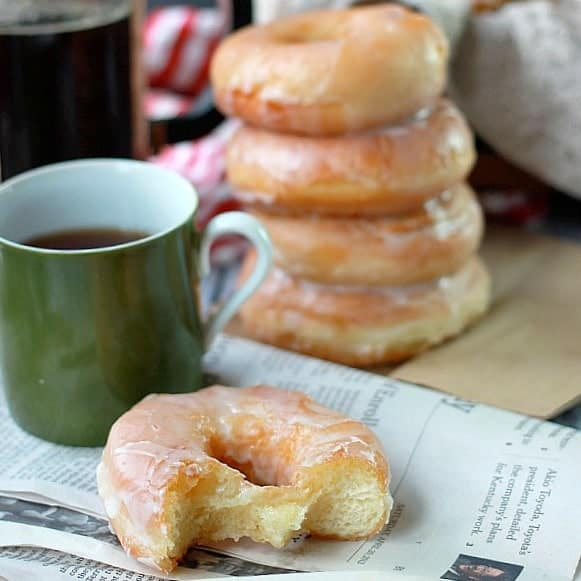 Stacked glazed donuts with cup of coffee and newspaper