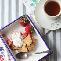 A slice of Paleo Strawberry Rhubarb Pie with Coconut Whipped Cream on a plate with a cup of tea