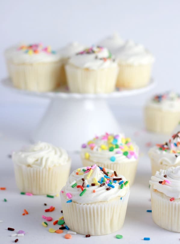 White Cupcakes topped with white buttercream and colorful sprinkles, some on a cake stand