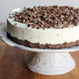 Easy No-Bake Cheesecake on a cake stand topped with peanut butter cups and shaved chocolate