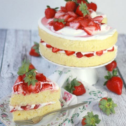 Lemon Strawberry Cream Cake on a cake stand with a slice cut out
