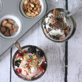 Frozen yogurt in cups topped with fruit, sprinkles, nuts, chocolate, etc.