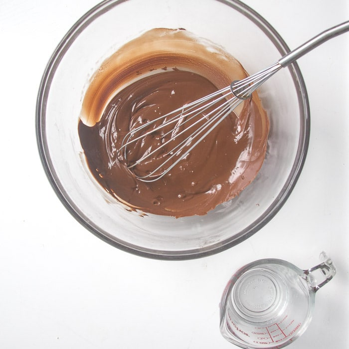Melted chocolate beside a cup of water