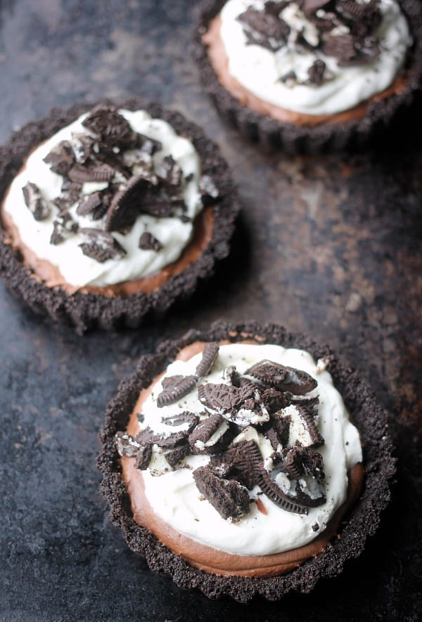 Oreo crusted tarts filled with chocolate mousse topped with whipped cream and crushed oreos