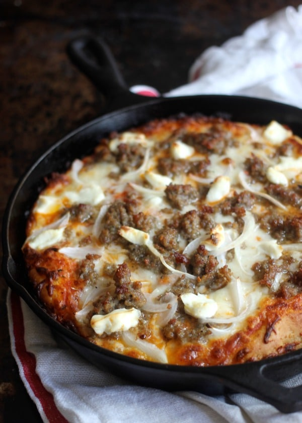 Baked pan pizza in the skillet topped with sausage and onion