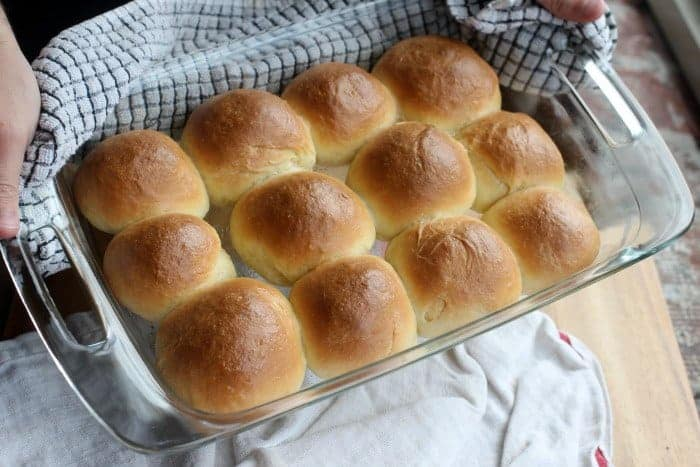 Me holding a glass baking dish of Soft Sour Cream Dinner Rolls