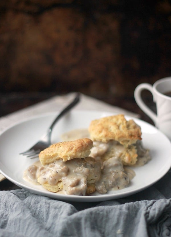 Biscuits sliced open and topped with gravy