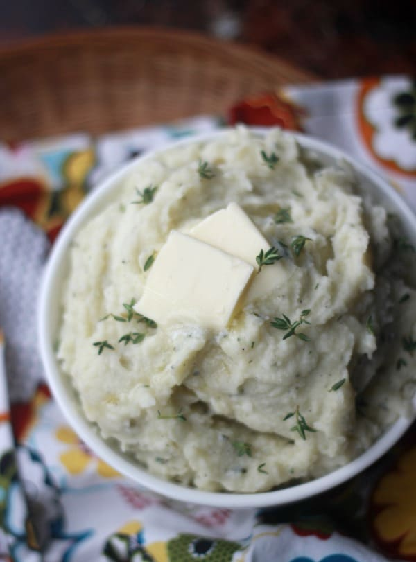 Creamy Herbed Mashed Potatoes in a bowl topped with a pad of butter