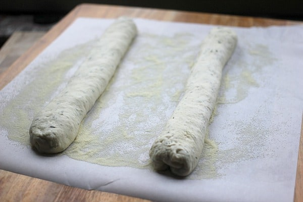 Dough logs sitting on top of parchment paper