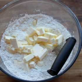 Fat being cut into dry ingredients with pastry cutter