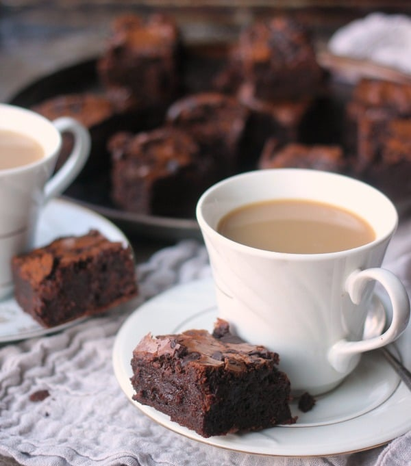 A brownie square with a cup of coffee