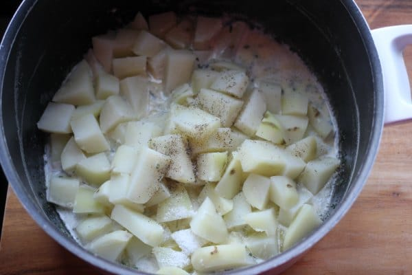 Drained soft potatoes added back to the pot with the herbs and butter