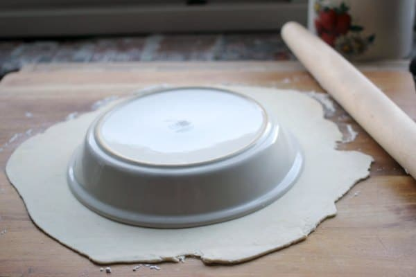 Pie crust rolled out with a pie tin on top to measure