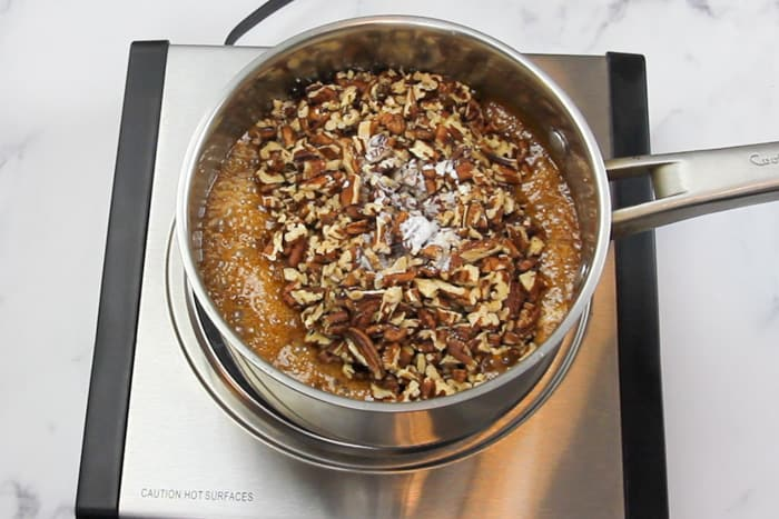 Pecans and cream being added to the caramel sauce