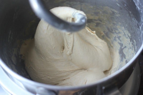 Pretzel dough being kneaded in a stand mixer with dough hook
