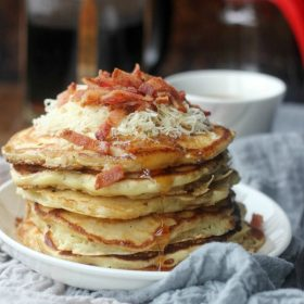Savory Bacon Cheddar Pancakes stacked up topped with cheddar and bacon crumbles