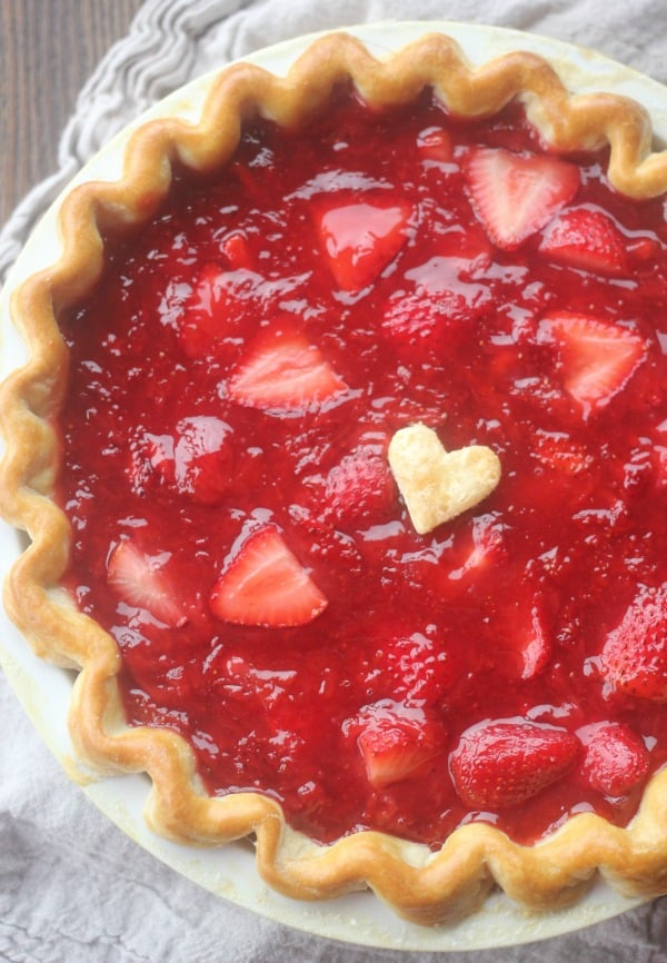 A whole Fresh Strawberry Pie with a heart shaped piece of pie crust as decoration on top