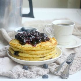 A stack of Fluffy Blueberry Buttermilk Pancakes topped with blueberry compote
