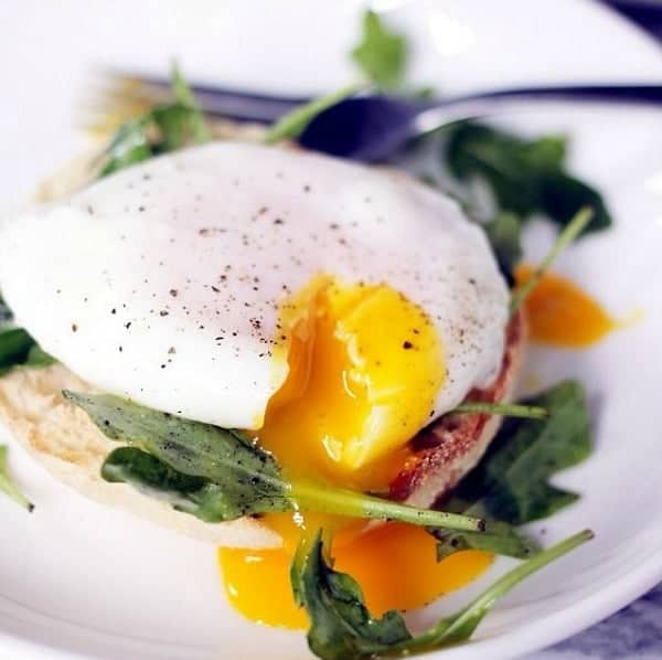 A runny poached egg on top of spinach and an english muffin