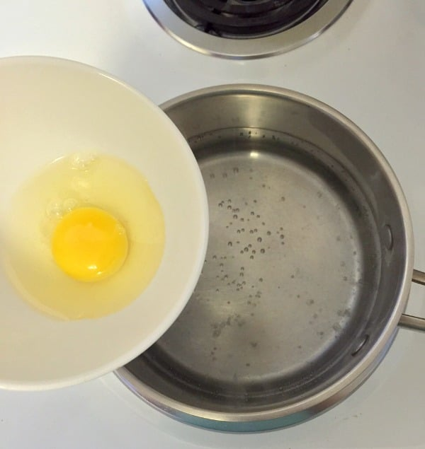 Raw egg in a bowl about to be gently poured into simmering water