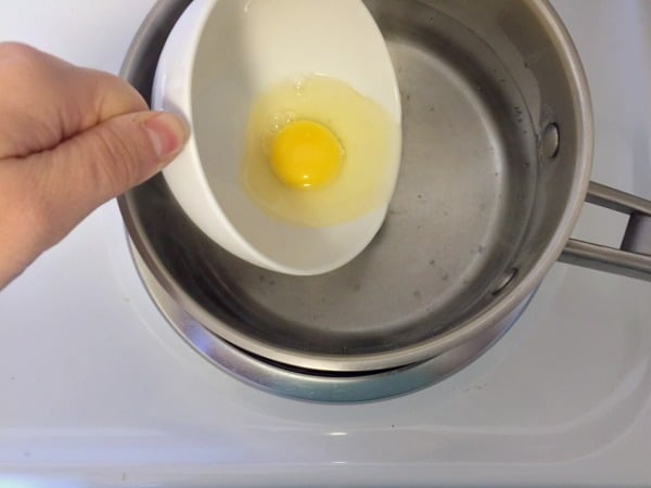 Gently tilting the raw egg into the simmering water