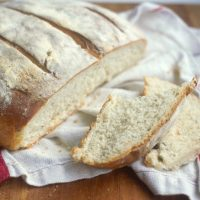 Rustic baked Yeast Bread lightly floured with a slice cut off