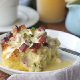 Eggs Benedict casserole on a plate topped with hollandaise sauce