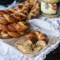 Dijon Stout Soft Pretzels stacked up and eaten with dijon mustard