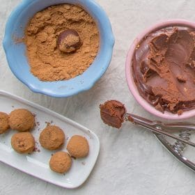 Chocolate truffles being scooped and rolled in cocoa powder