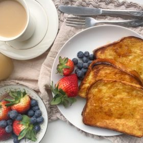 Crispy Oven Baked French Toast slices on a plate with fresh berries