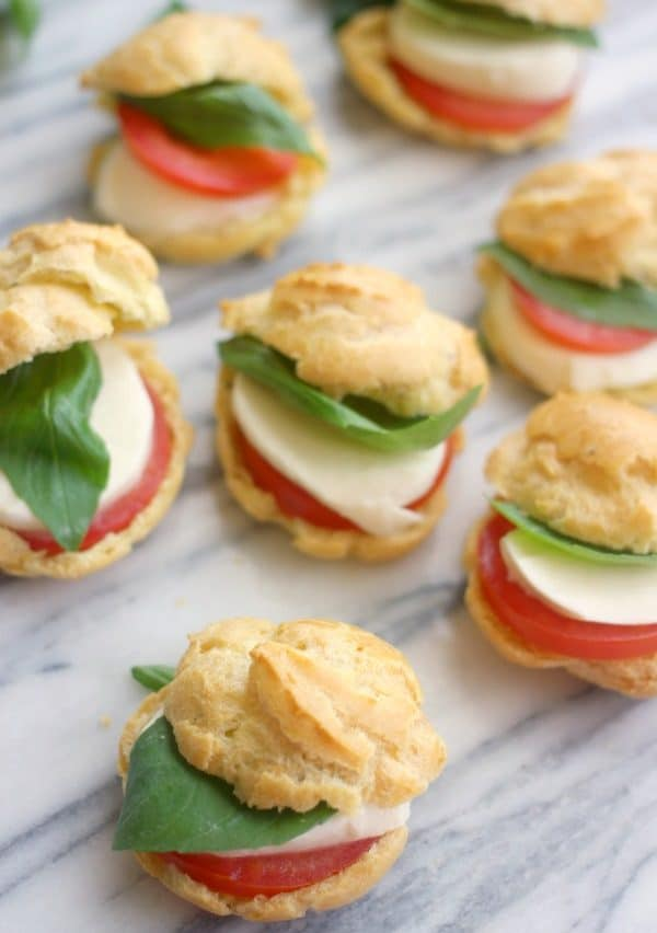 Profiteroles filled with slices of tomato, fresh mozzarella, and basil