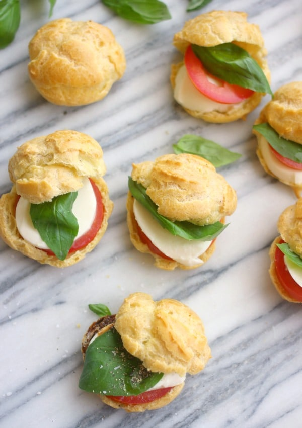 Savory Caprese Profiteroles are the perfect two bite treat for your summer gathering! The shells are made out of black pepper studded pate a choux shells and they are filled with slices of tomato, fresh mozzarella, and basil!