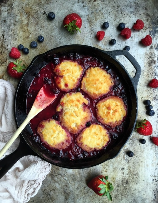 Triple berry cobbler is a very easy recipe to showcase all of those beautiful summer berries! Strawberries, blueberries, and raspberries are the stars in this simple cobbler that bakes in a cast iron skillet!