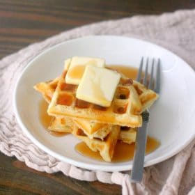 A stack of waffles with syrup and butter