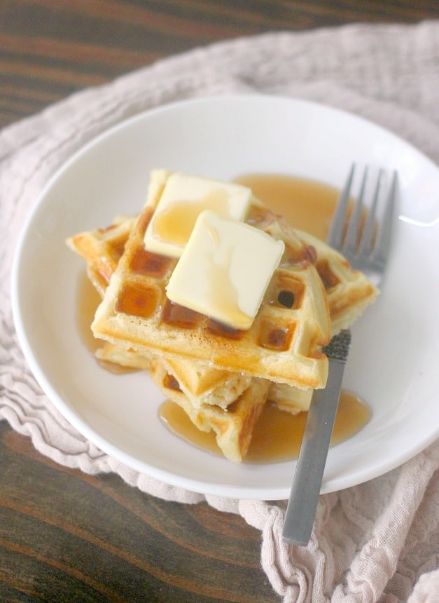 Waffles topped with butter and syrup on a plate