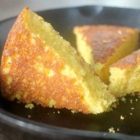 A wedge of cornbread in a skillet