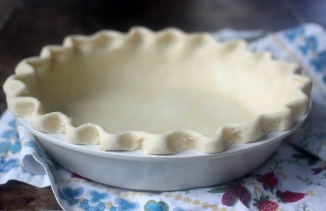 Raw pie crust crimped in pie plate