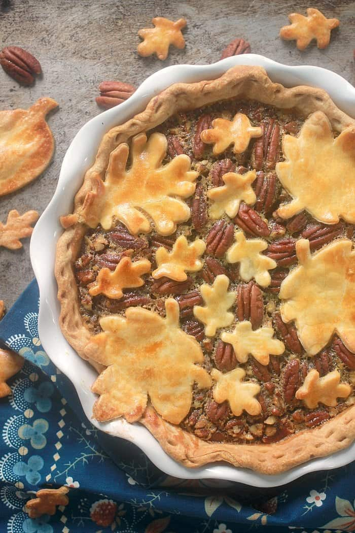 Salted maple pecan pie with decorative leaf pie pieces on top. Pie pieces and pecan are also laying around the pie.