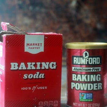 Box of baking soda and a can of baking powder side by side