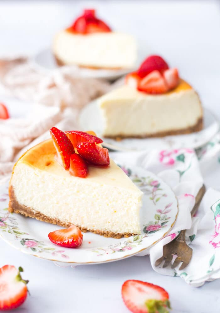 Slices of New York Style cheesecake plated up with fresh strawberries