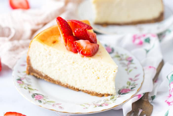 Slice of New York Style Cheesecake plated up with fresh strawberries