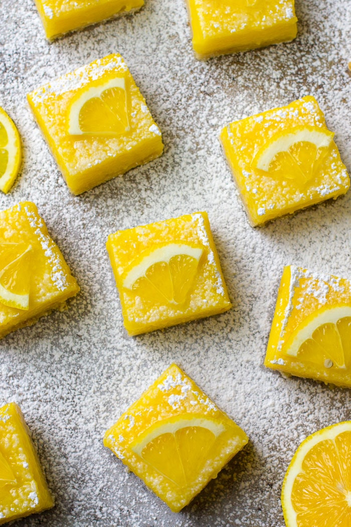 Lemon Bar squares decorated with a lemon slice and sprinkled with powdered sugar