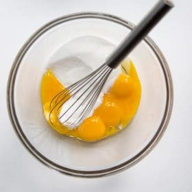 Egg yolks and sugar in a bowl with a whisk