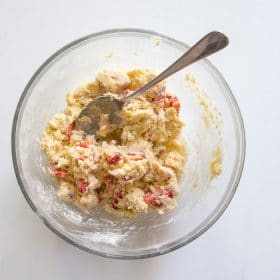 Wet ingredients and dry ingredients mixed together to form a shaggy dough for strawberries and cream scones