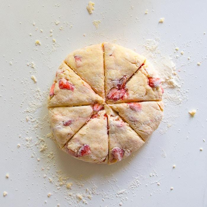 Raw strawberry scone dough cut into 8 triangles