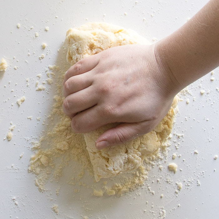 Create layers in the dough by pressing down and folding the dough