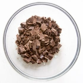 Cut up chocolate in glass bowl